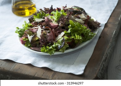 Beef and mixed leaf salad on a white plate with parmasan and capers