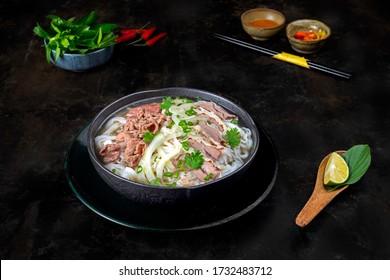 Nouille de boeuf ou Pho Bo dans une table de cuisine sombre de classe cuisine. La nourriture est de l'herbe dans un délicieux bouillon. Servir avec du chili, de la sauce au chili, de la chaux. Meilleur street food du Vietnam
