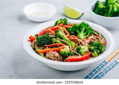 Beef Noodle Stir Fry with broccoli, carrots and red bell peppers on gray stone background