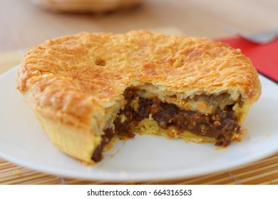Beef pie on white plate close up