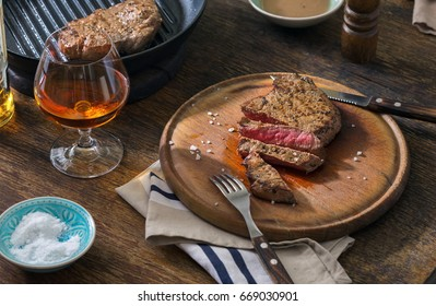 Beef rare grilled steak on wooden board with glass of whiskey close up