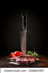 Beef rare steak on a wood desk with chef knife. Around are fresh tomatoes, sweet and spicy peppers, greens and spices, white salt and black pepper. Ideal for the restaurant menu or for intr