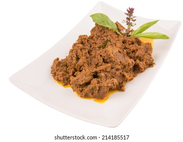 The Beef Rendang, a popular traditional Malay dish on white plate over white background