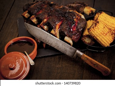 Beef ribs cooked on the BBQ and served with sweetcorn and a red wine souse. Barbequed beef ribs and corn.