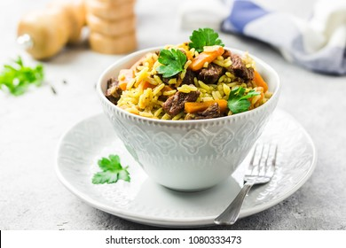 Beef rice pilaf in a bowl on light concrete background. Selective focus, space for text.