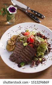 Beef salad: grilled beef steaks with tomatoes, cucumbers, zucchini, lettuce and cabbage, sprinkled with flax seeds. Vertical image