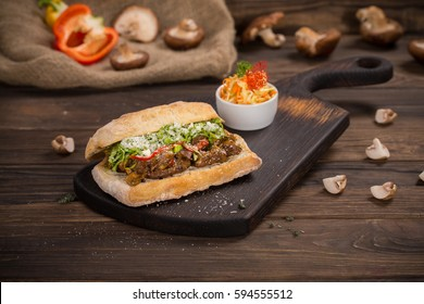 Beef sandwich with mushrooms on dark wooden cutting board. Wooden rustic table top.