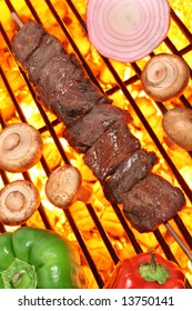 Beef shish kebab veggies on a fire hot barbecue grill.