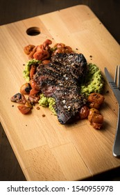 Beef sirloin steak on cutting board with avocado puree, melted tomatoes, salt and pepper on dark wooden background