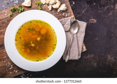 Beef soup with carrots and herbs on a dark background, top view