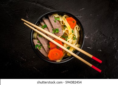 Beef soup with noodles and carrots in the Asian style. With chopsticks, on the black concrete table, top view, copy space