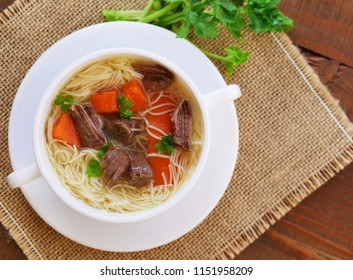 Beef soup with noodles and vegetables in soup bowl over wooden table top view