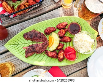 Beef steak with chicken wings and fruits, top view