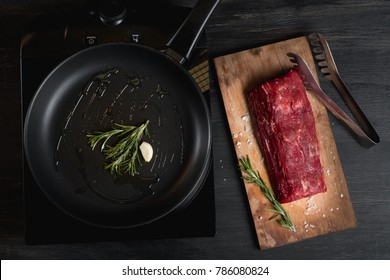 Beef steak filet wellington sliced on a chopping board on black background.