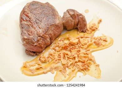Beef steak with fried onions and mustard