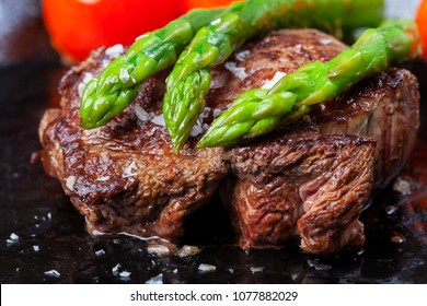 beef steak and green asparagus in a pan