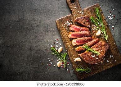 Beef steak. Grilled meat at wooden cutting board. Top view image with copy space.