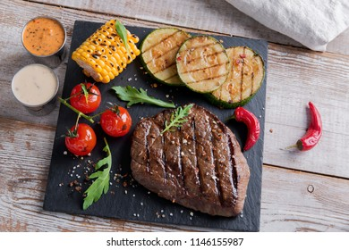 beef steak with grilled vegetables on a stone surface