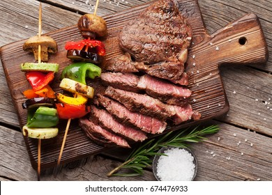 Beef steak and grilled vegetables on cutting board on wooden table. Top view