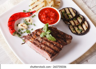 beef steak, grilled vegetables and sauce on a plate close-up. horizontal view from above