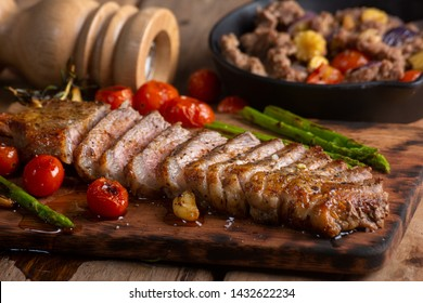 Beef Steak with Herbs and Spices on cutting board. and Fried pork with clam sauce Side dish.