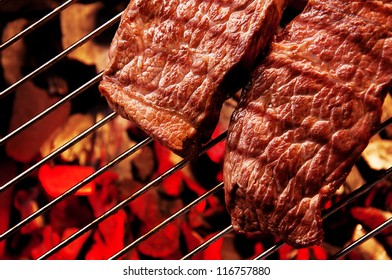 Beef steak meat on BBQ Barbecue grid.
