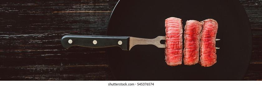 beef steak on a fork on a dark wooden background