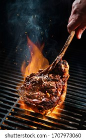 Beef steak on the grill with smoke and flames