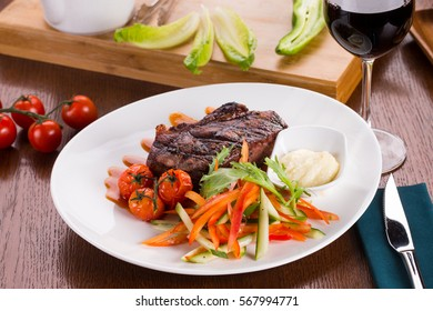 Beef steak on white plate. Black angus meet dish. Glass of red wine in soft focus.