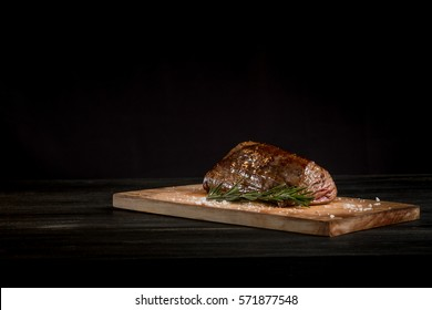 Beef steak on the wood black background with free space for text design or logotype menu restaurant. Horizontal photo. Food background. Black text area.