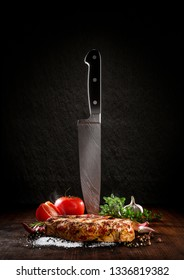 Beef steak on a wood desk with chef knife. Around are fresh tomatoes, sweet and spicy peppers, greens and spices, white salt and black pepper. Ideal for the restaurant menu or for intr