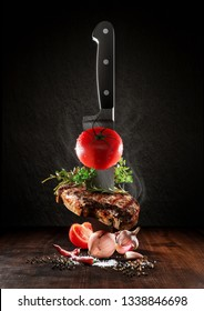 Beef steak on a wood desk with chef knife. Around are fresh tomatoes, sweet and spicy peppers, greens and spices, white salt and black pepper. Creative composition