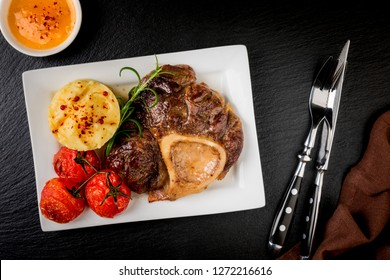 Beef steak osso bucco with mashed potatoes and tomatoes on dark table. Dish with meat. Top view
