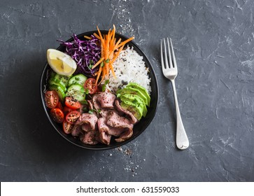 Beef steak, rice and vegetable power bowl. Healthy balanced food concept. On a dark background, top view