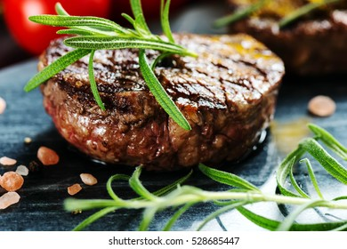 Beef steak with rosemary on marble cutting board.