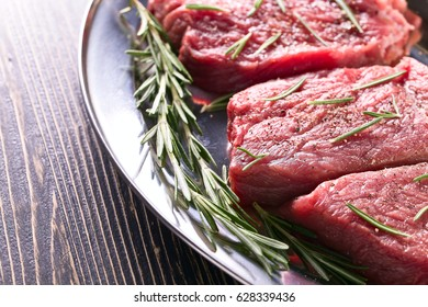 Beef steak with rosemary , salt and pepper on a old wooden table .