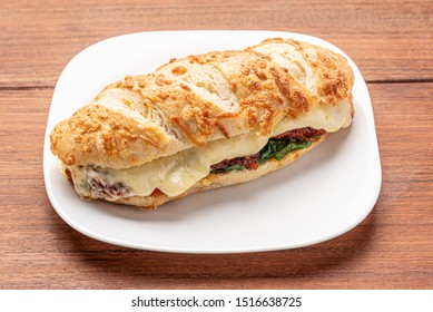 Beef steak sandwich with cheese and tomato, isolated on wooden background