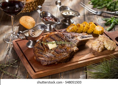 Beef steak with sauces on wooden cutting board with red wine on soft focus on wooden table top.