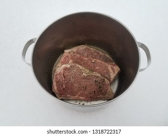 beef steak with seasoning and liquid in metal pot on snow
