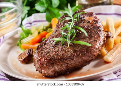 Beef steak served with baked potatoes and vegetables