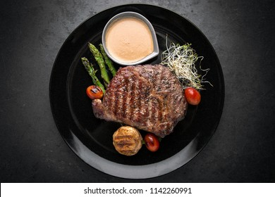 Beef steak with spices, grilled vegetables, asparagus and cream sauce. Gourmet dish