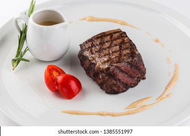 Beef steak with spices served on a dish of white background. A piece of tenderloin beef. Filet Mignon.