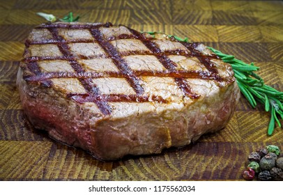 Beef steak with twig rosemary on a wooden table. Juicy toasted piece of steak meat.
