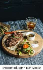 Beef steak with vegetables and chili sauce served on a board on a wooden background with glass of whiskey