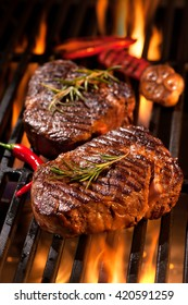 Beef steaks on the grill with flames