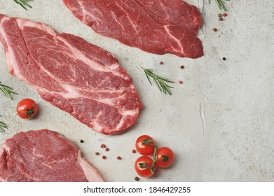 Beef steaks on a light background.  Rosemary, spices and cherry tomatoes complete the composition.  View from above.  Free space for text placement.