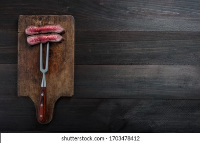 Beef steaks rib eye fried on grille, culinary background. Grilled meat on wooden cutting board with rosemary, flat lay
