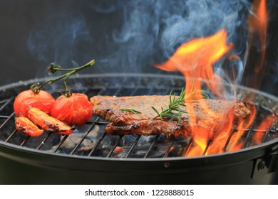 Beef steaks with rosemary on grill with flame and smoke on dark background, food meat or barbecue