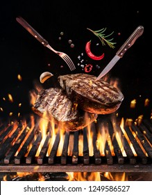 Beef steaks with vegetables and spices fly over the blazing grill barbecue fire. Concept of flying food.