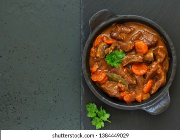 Beef stew in Burgundy. With carrots, onions, peas and champignons in wine. View from above.